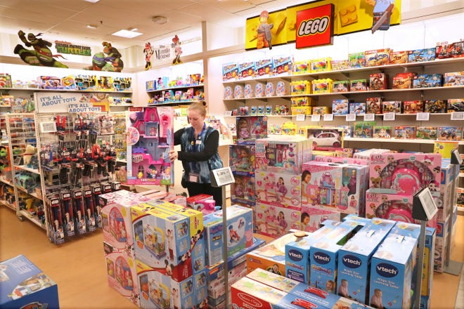 Kohl's employee Amanda Patch sets up a display in the toy section of the Kohl's store in Sussex.