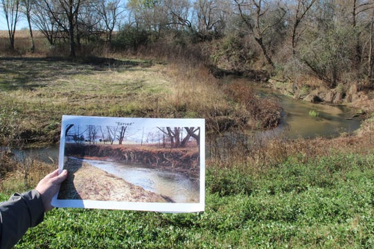 A photo showing an eroded bank on a section of Beaver Creek outside Sparta is held for comparison with the current, rehabilitated condition of the stream.