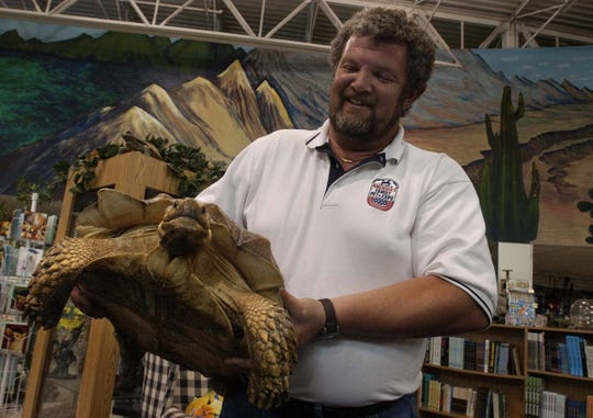 Mike Hoffer, owner of Hoffer's Tropical Life Pets in Milwaukee, holds Spanky, a 30 pound, African spur-thighed tortoise at his store Tuesday, June 10, 2003.  Hoffer died on Oct. 17, 2018.