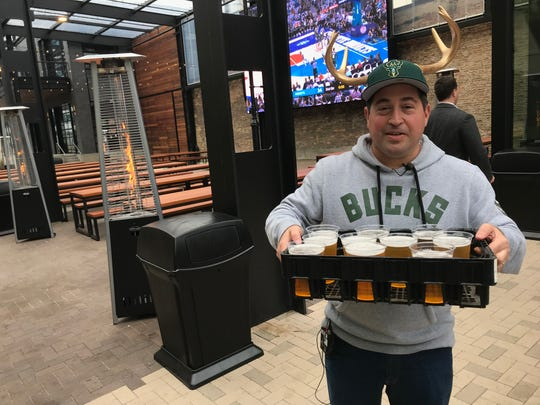 Milwaukee Bucks President Peter Feigin hands out beer at the grand opening of the beer garden outside Fiserv Forum.