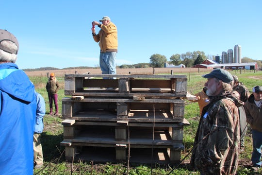 Duke Welter of Trout Unlimited takes a photograph from atop wooden structures used to improve fish habitat in streams during a tour of the Driftless Area.