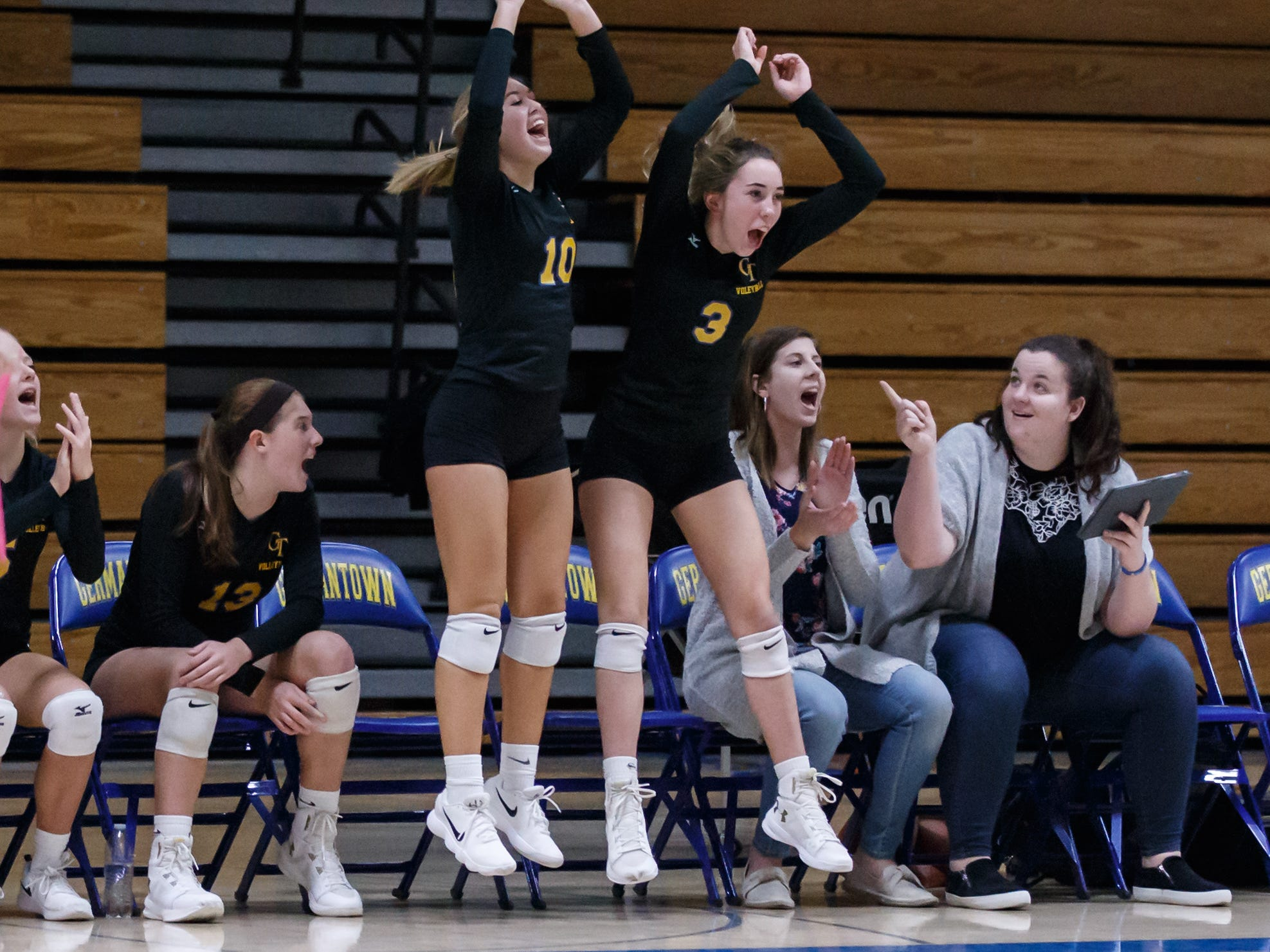 Germantown players Julia Maas (10) and Halee Behrens (3) celebrate winning the first set during the WIAA Regional match at home against Homestead on Thursday, Oct. 18, 2018. Germantown won the match 25-21, 25-12, 25-18.