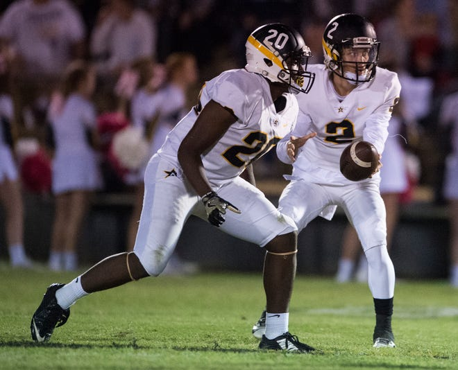 Autauga's Tripp Carr (2) hands the ball off to Autauga's Derrion Ashley (20) at Autauga Academy in Prattville, Ala., on Thursday, Oct. 18, 2018.