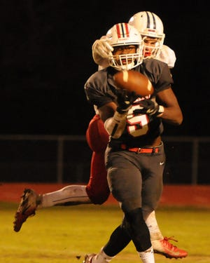 Oakland's Tekoy Randolph hauls in a pass while being draped by Cookeville's Jacob Stamps (4).