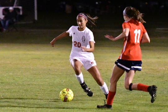 Stewarts Creek's Sabrina White looks upfield as Oakland's Madeline Myers defends during a 2018 match.