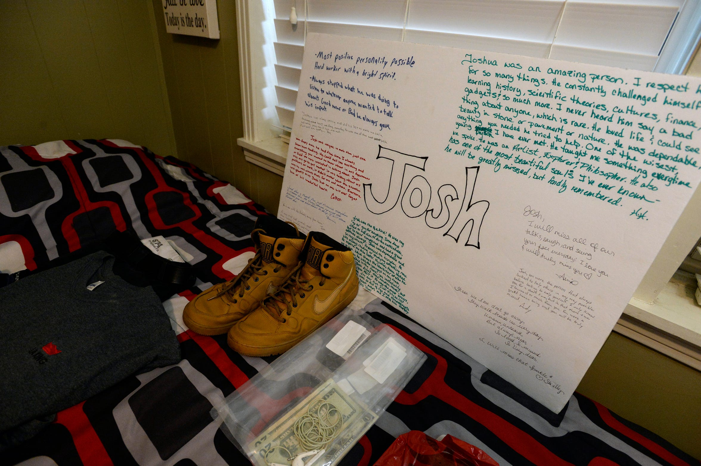 The clothes Josh Holton was wearing when he died and a memorial poster made by his co-workers are displayed on his bed Thursday, Oct. 18, 2018. Holton overdosed in 2016 after he bought what he thought was Xanax on the darkweb but received fentanyl.