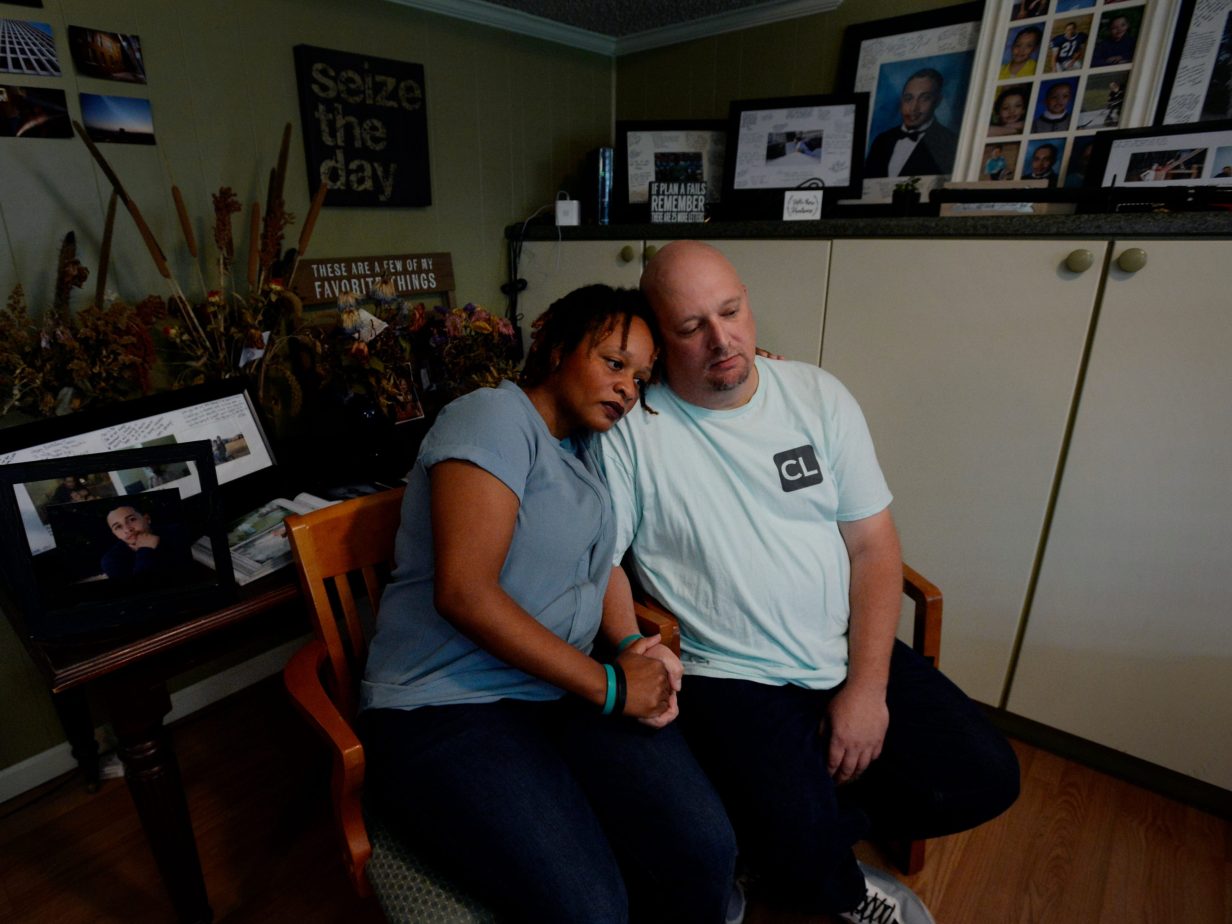 Rachel and Michael Blado hold hands, surrounded by photos of their son Josh Holton, at their home in Antioch on Oct. 18. Holton died of a drug overdose in 2016 after he bought Xanax online but received a deadly fentanyl pill instead.