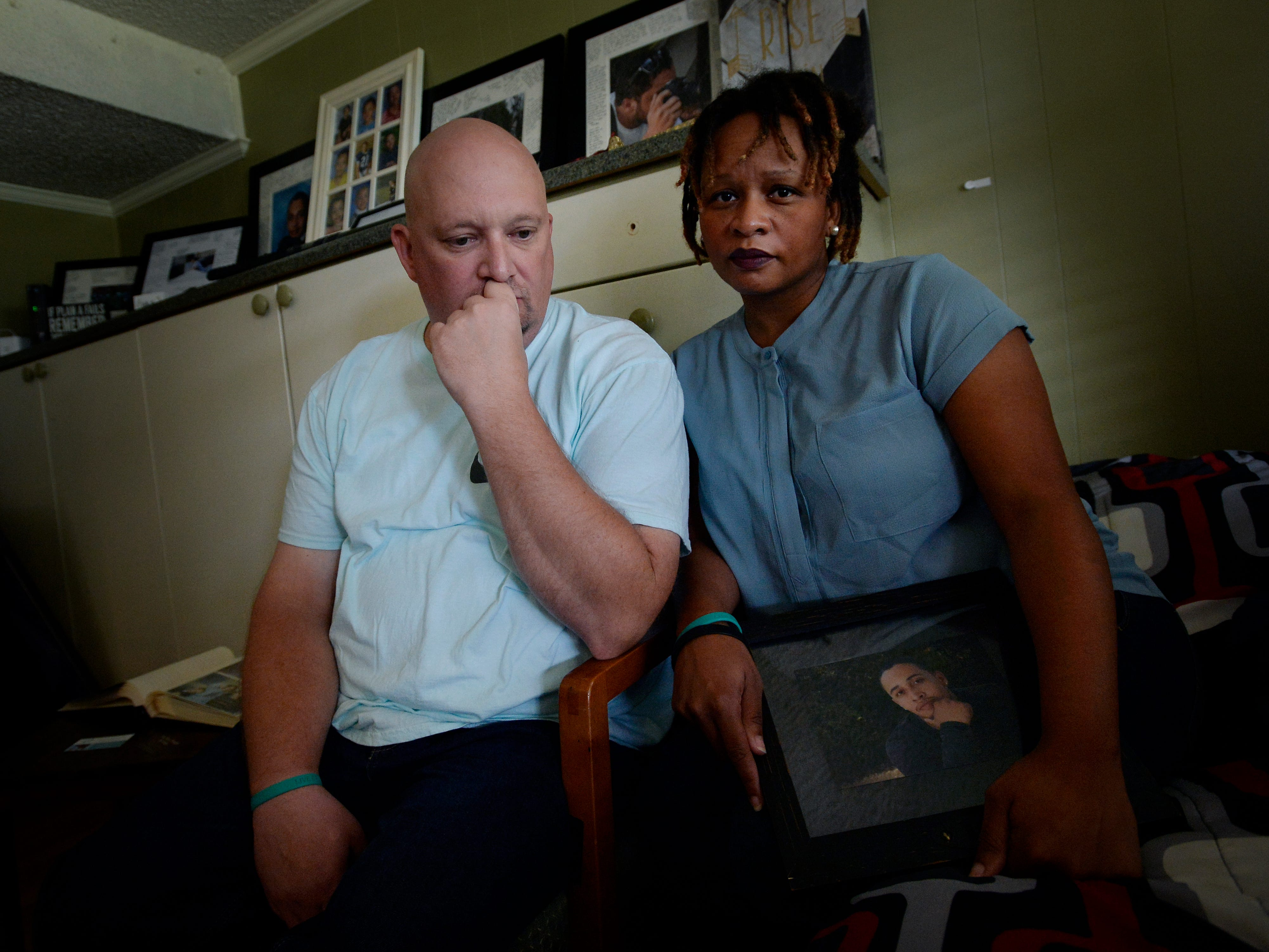 Michael Blado and his wife Rachel hold a photograph of their son Josh Holton as they sit in his bedroom on Thursday, Oct. 18, 2018, in Nashville, Tenn. Holton overdosed in 2016 after he bought Xanax on the Dark Web to self-medicate for insomnia but the pills he received contained fentanyl causing his death.