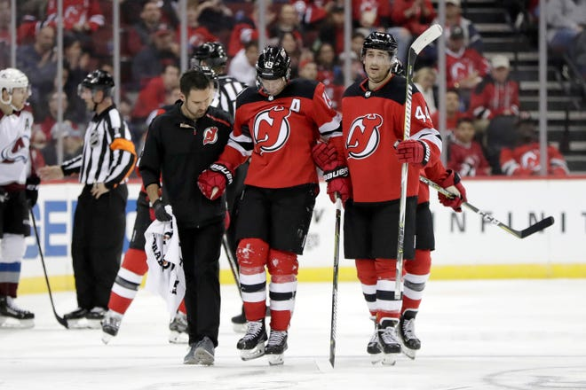 New Jersey Devils center Travis Zajac, center, is helped off the ice by left wing Miles Wood (44) after taking a hit against the Colorado Avalanche during the second period of an NHL hockey game, Thursday, Oct. 18, 2018, in Newark, N.J.