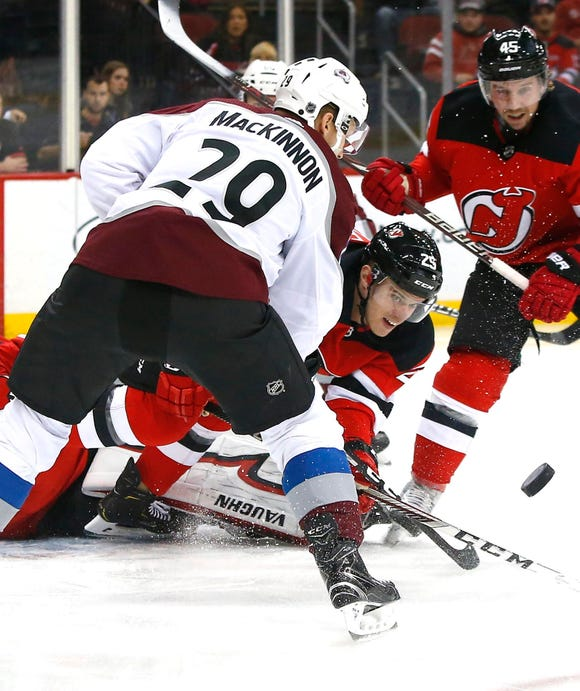 Oct 18, 2018; Newark, NJ, USA; New Jersey Devils defenseman Mirco Mueller (25) and Colorado Avalanche center Nathan MacKinnon (29) battle for the puck during first period at Prudential Center.