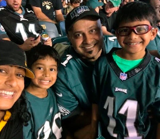 In this August 2018 photo provided by Nima Desai, Philadelphia Eagles fan Jigar Desai, center, poses with his wife Nima and their children at a Eagles verses Pittsburgh Steelers football game at Lincoln Financial Field in Philadelphia. The moment in the spotlight isn't over yet for Jigar Desai, who stumbled into fame as a viral video star after running into a subway pillar earlier this year. Desai is now the subject of an NFL digital short feature, shot ahead of the  Oct 28 Eagles game against the Jacksonville Jaguars in London.  (Nima Desai via AP)