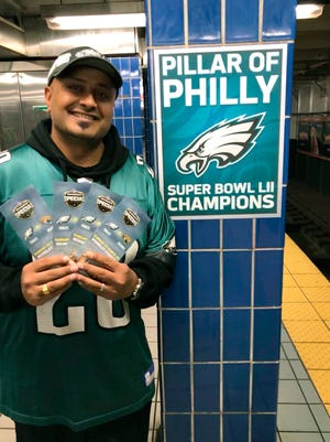 In this October 2018 photo provided by Matt Liston, Philadelphia Eagles fan Jigar Desai poses with tickets to an Oct. 28 football game between the Eagles and the Jacksonville Jaguars in front of the subway pillar he ran into earlier this year at Ellsworth Station on the Broad Street subway line in Philadelphia. The moment in the spotlight isn't over yet for Desai who stumbled into fame as a viral video star after running into the subway pillar. Desai is now the subject of an NFL digital short feature, shot ahead of the Oct. 28 Eagles game against the Jacksonville Jaguars in London. (Matt Liston via AP)