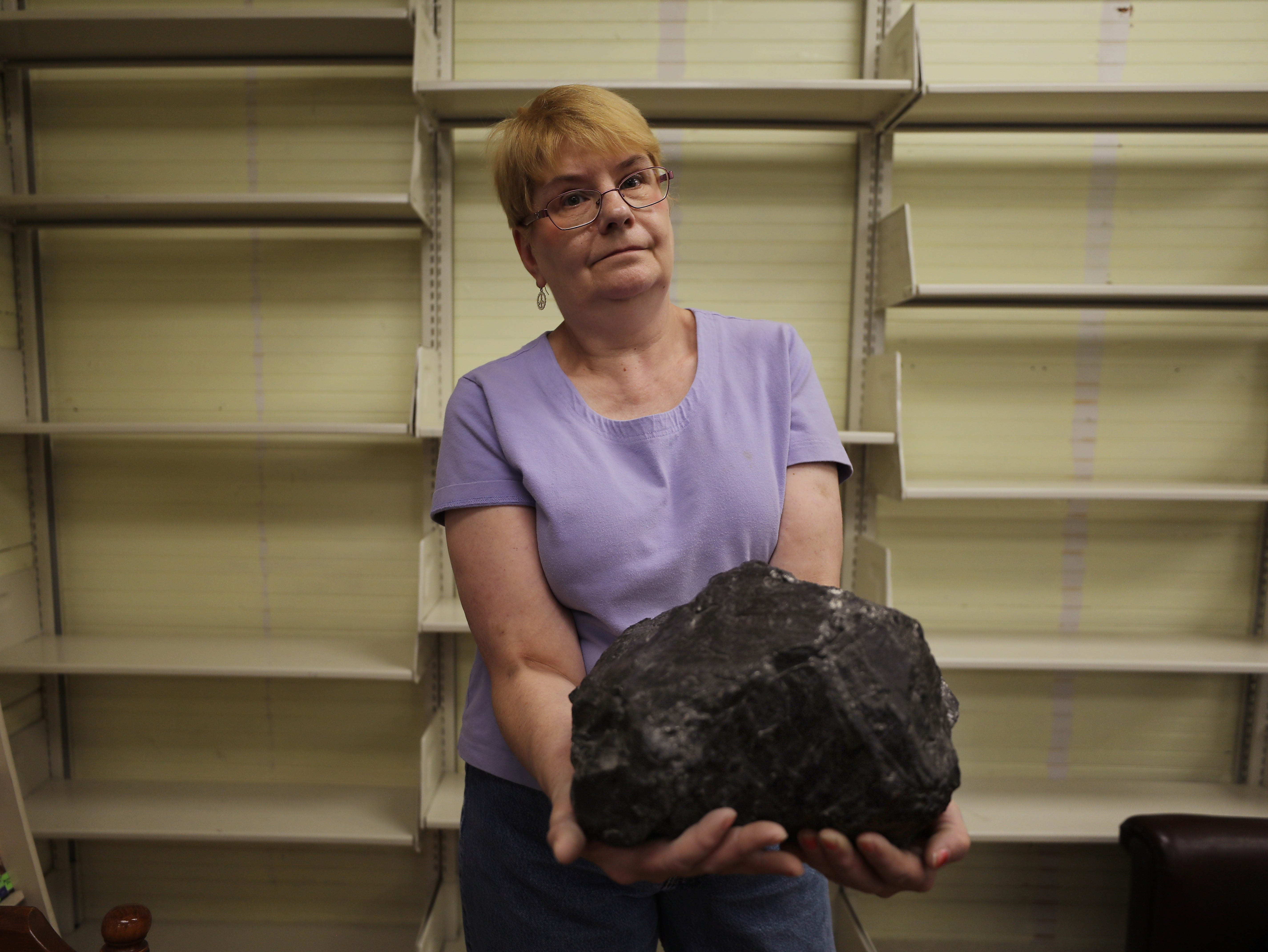 Marianna librarian Pamela Clutter holds a large piece of coal in the small library where she works. The coal serves as a learning aid as she teaches students about the history of the town and its once-thriving coal industry.