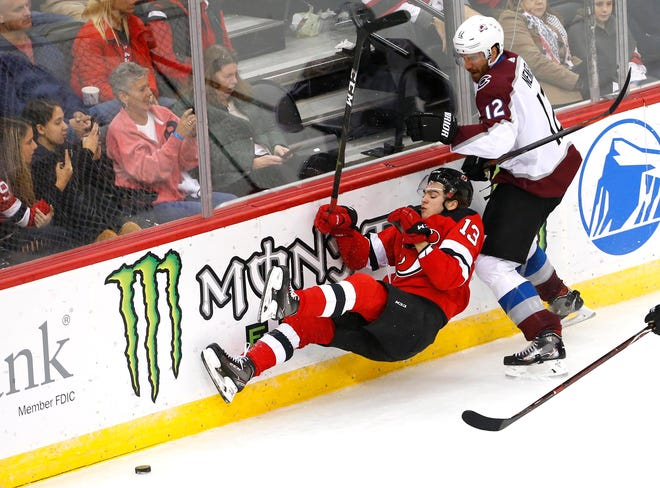 Oct 18, 2018; Newark, NJ, USA; New Jersey Devils center Nico Hischier (13) goes down after a check by Colorado Avalanche defenseman Patrik Nemeth (12) during the third period at Prudential Center.