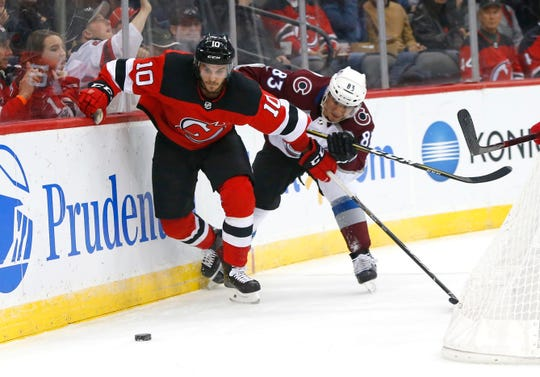 Oct 18, 2018; Newark, NJ, USA; New Jersey Devils center Jean-Sebastien Dea (10) and Colorado Avalanche left wing Matt Nieto (83) battle for the puck during first period at Prudential Center.
