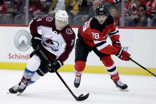 Colorado Avalanche left wing Matt Calvert (11) skates against New Jersey Devils defenseman Damon Severson (28) during the first period of an NHL hockey game, Thursday, Oct. 18, 2018, in Newark, N.J.