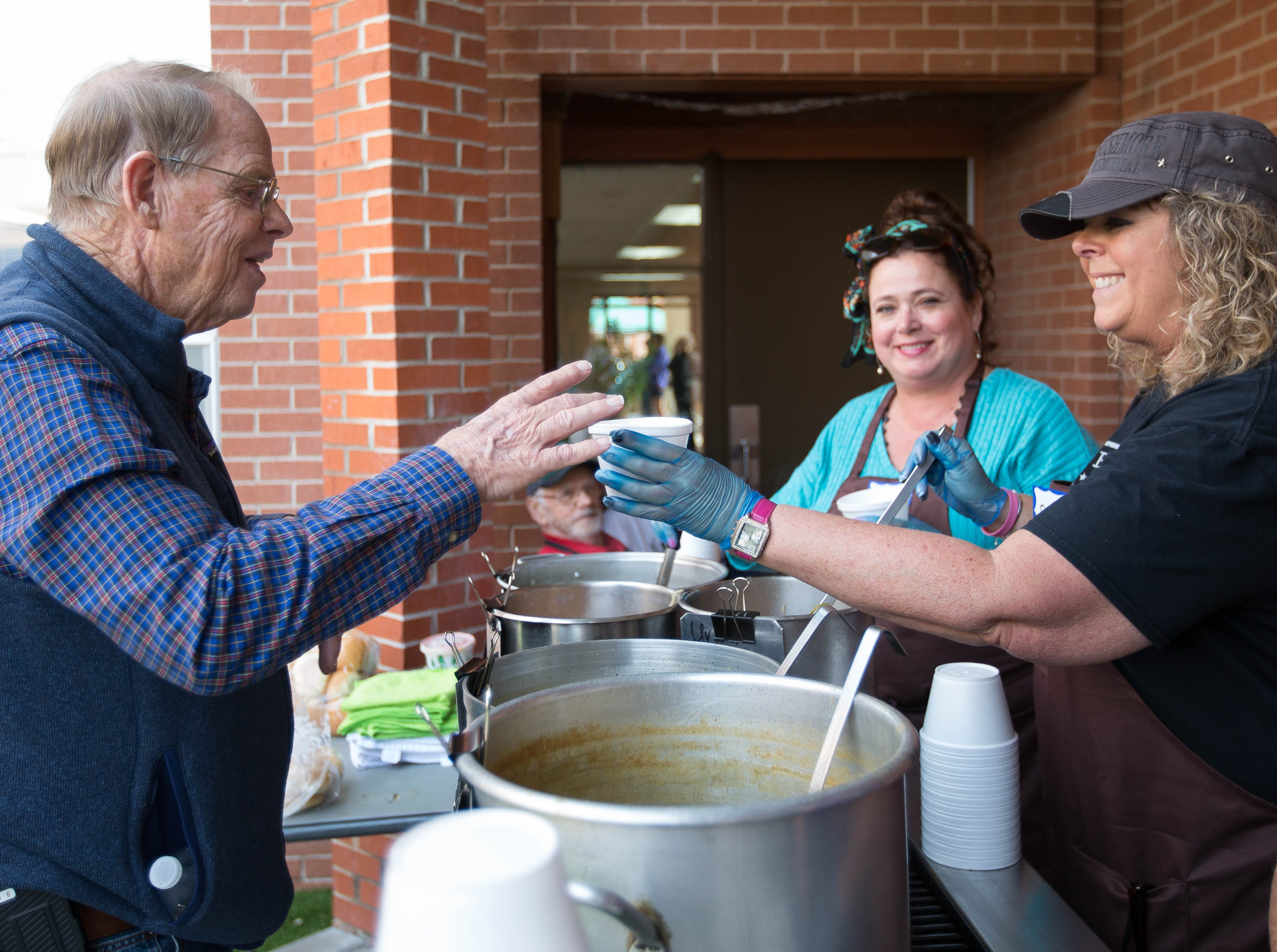 Delyce Maciel, right, hands a bowl of Chicken Caldo to Bill Seiffert, Friday October 19, 2018 during the El Caldito Soup Kitchen and Potters'  Guild of Las Cruces' 26th Annual Empty Bowls event at St. Paul's Methodist Church.