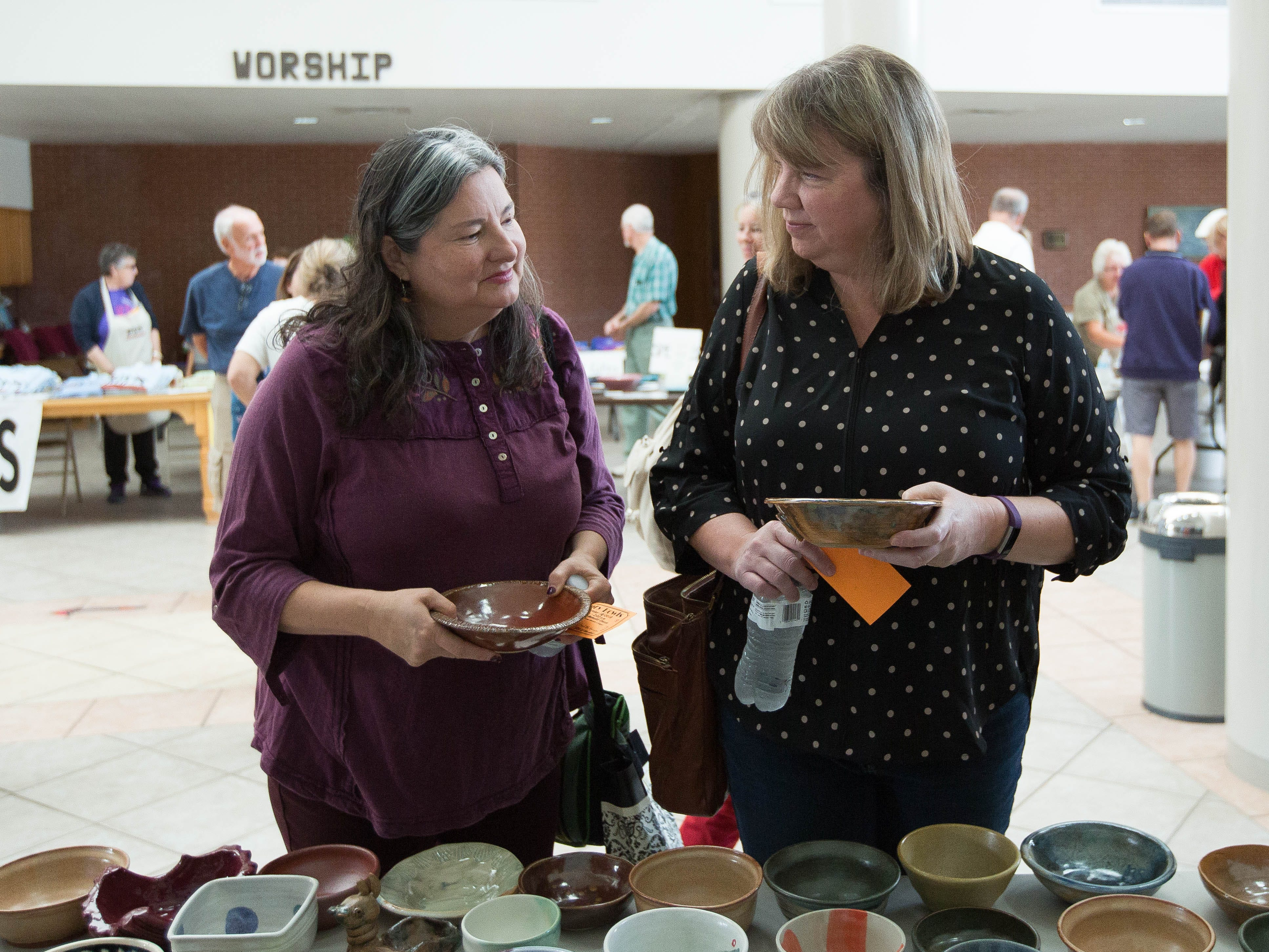 Jill Gladstone, right, and Linda Flores, left, look through the hand made bowls by the Potters' Guild of Las Cruces, before picking out the ones they wanted to keep, Friday October 19, 2018, at the  St. Paul's United Methodist Church.