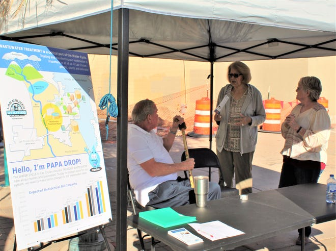 Utilities customer Olga Sakellanos chats with UCAG Chairman Eugene Suttmiller and Vice-Chairwoman Shirley Clark at the Farmer's Market. The UCAG is seeking active input on a proposed rate hike..