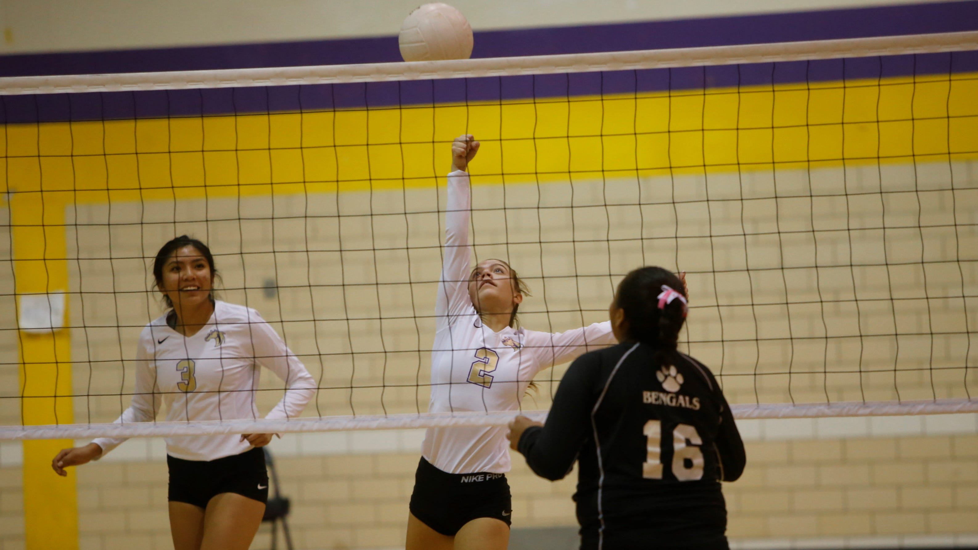 Kirtland Central's Peanut Dryden punches the ball over the net against Gallup's Hailey Long (16) during Thursday's District 1-4A match at KCHS.