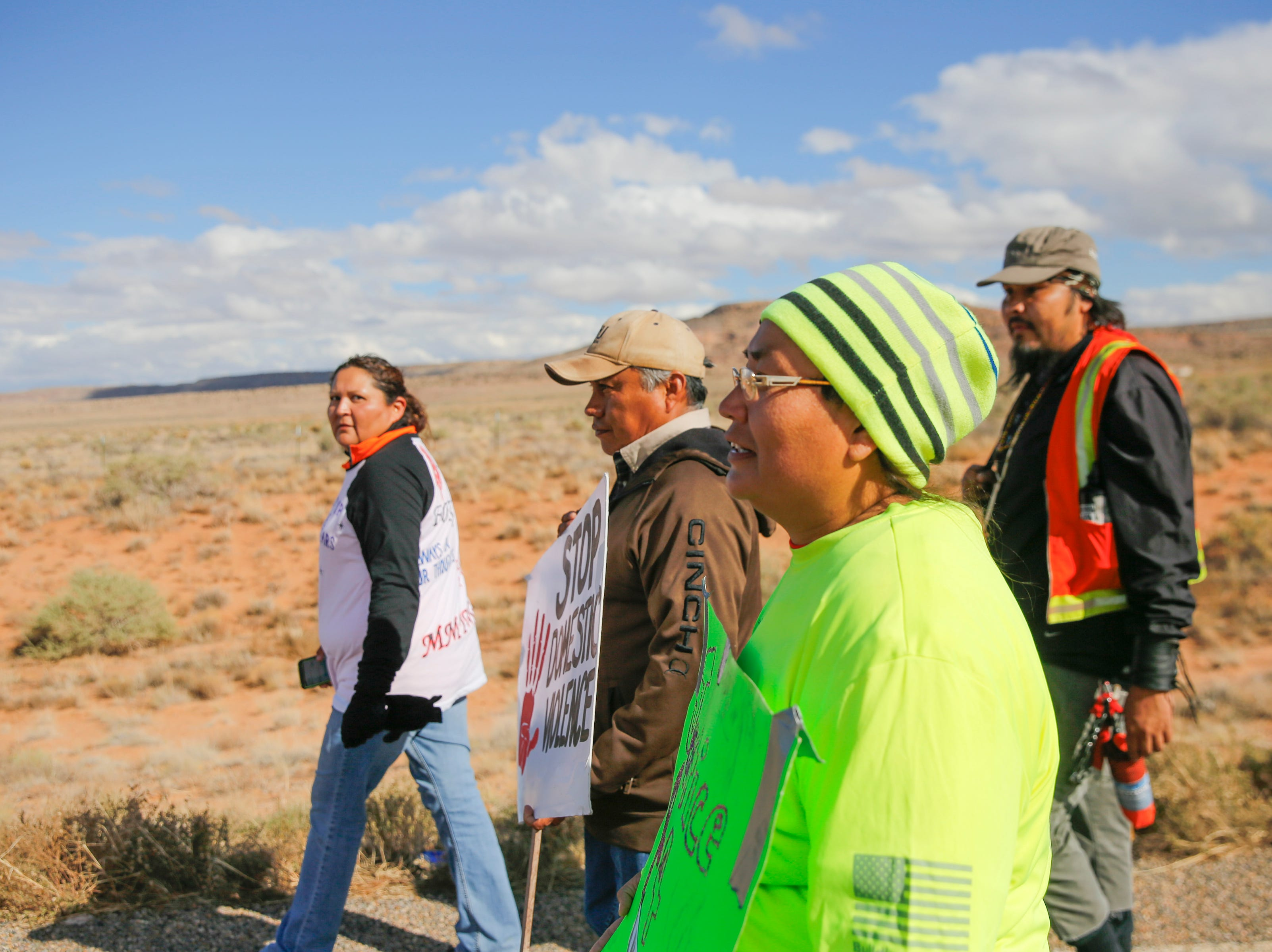 From left, Johannah Barber, Jerald Begay, Sarah Begay and Bobby Mason participate in an awareness walk organized by Walking the Healing Path, Thursday, Oct. 18, 2018 along Navajo Route 13 in Red Valley, Arizona.