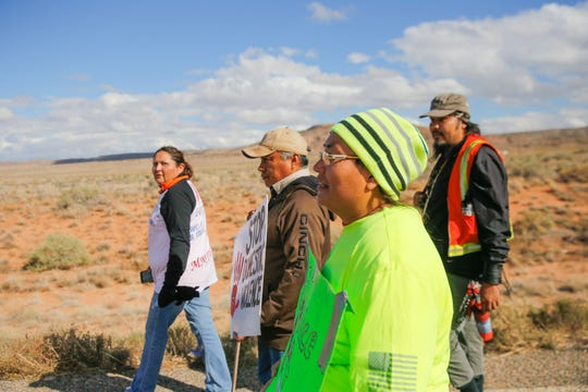 Johannah Barber, left, Jerald Begay, Sarah Begay and Bobby Mason participate in an awareness walk organized by Walking the Healing Path Thursday along Navajo Route 13 in Red Valley, Ariz.