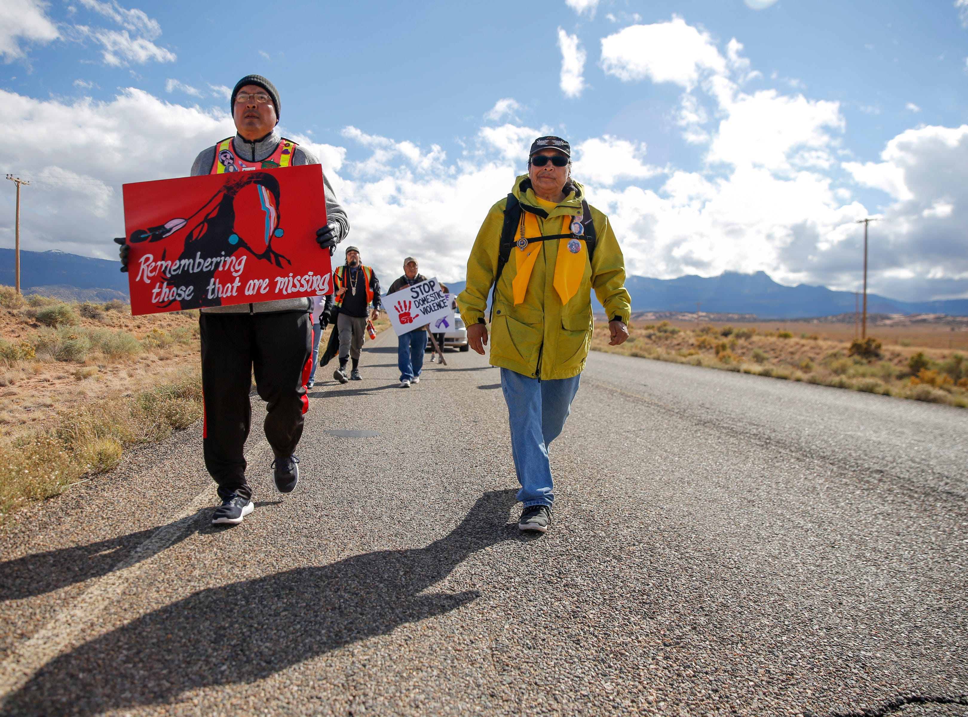 John Tsosie, co-founder of Walking the Healing Path, left, and Gary Mike, father of Ashlynne Mike, walk along Navajo Route 13 in Red Valley, Arizona on Thursday, Oct. 18, 2018. Community members are walking from Window Rock, Arizona to Shiprock to bring awareness about the issue of murdered and missing indigenous women. Gary Mike is walking the entire route and has been talking about children safety during presentations by the group.