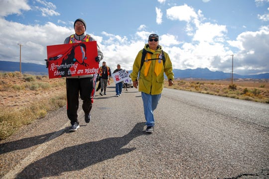John Tsosie, co-founder of Walking the Healing Path, left, and Gary Mike, father of Ashlynne Mike, walk along Navajo Route 13 in Red Valley, Ariz., on Thursday.