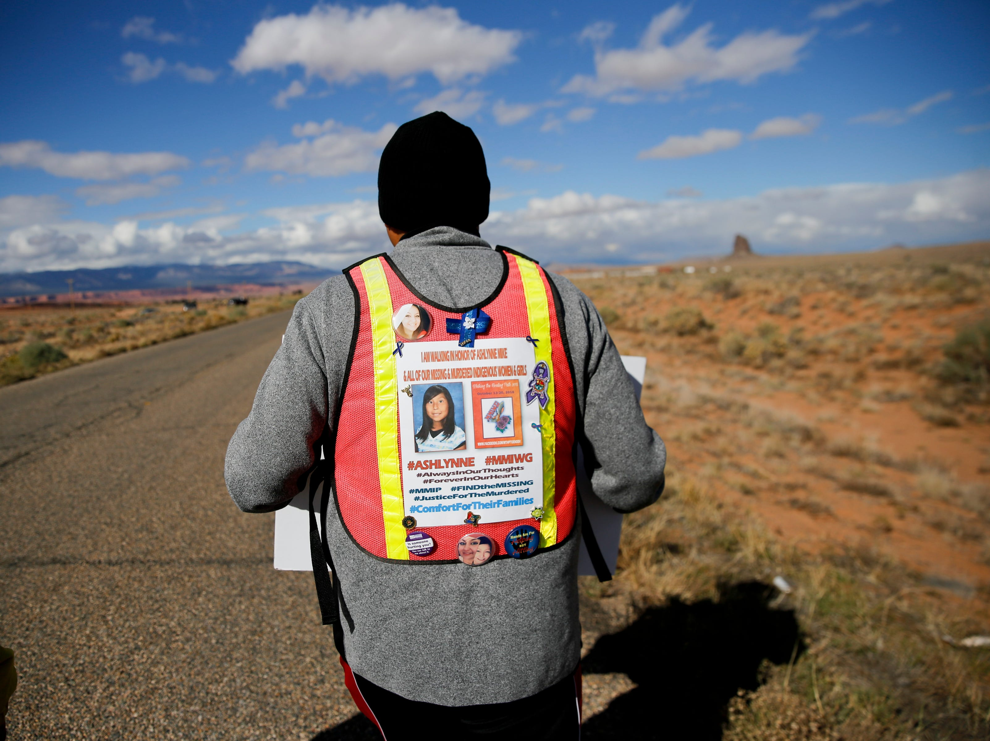 John Tsosie, co-founder of Walking the Healing Path walks along Navajo Route 13, Thursday, Oct. 18, 2018 in Red Valley, Arizona. Tsosie said the walk is underway to bring awareness about murdered and missing indigenous women. It is also dedicated to Ashlynne Mike after Tsosie received permission from Gary Mike and Pamela Foster to include their daughter for the event.