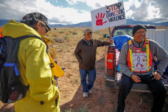 Gary Mike, left, Jerald Begay and John Tsosie break for lunch along Navajo Route 13 in Red Valley , Ariz., Thursday.
