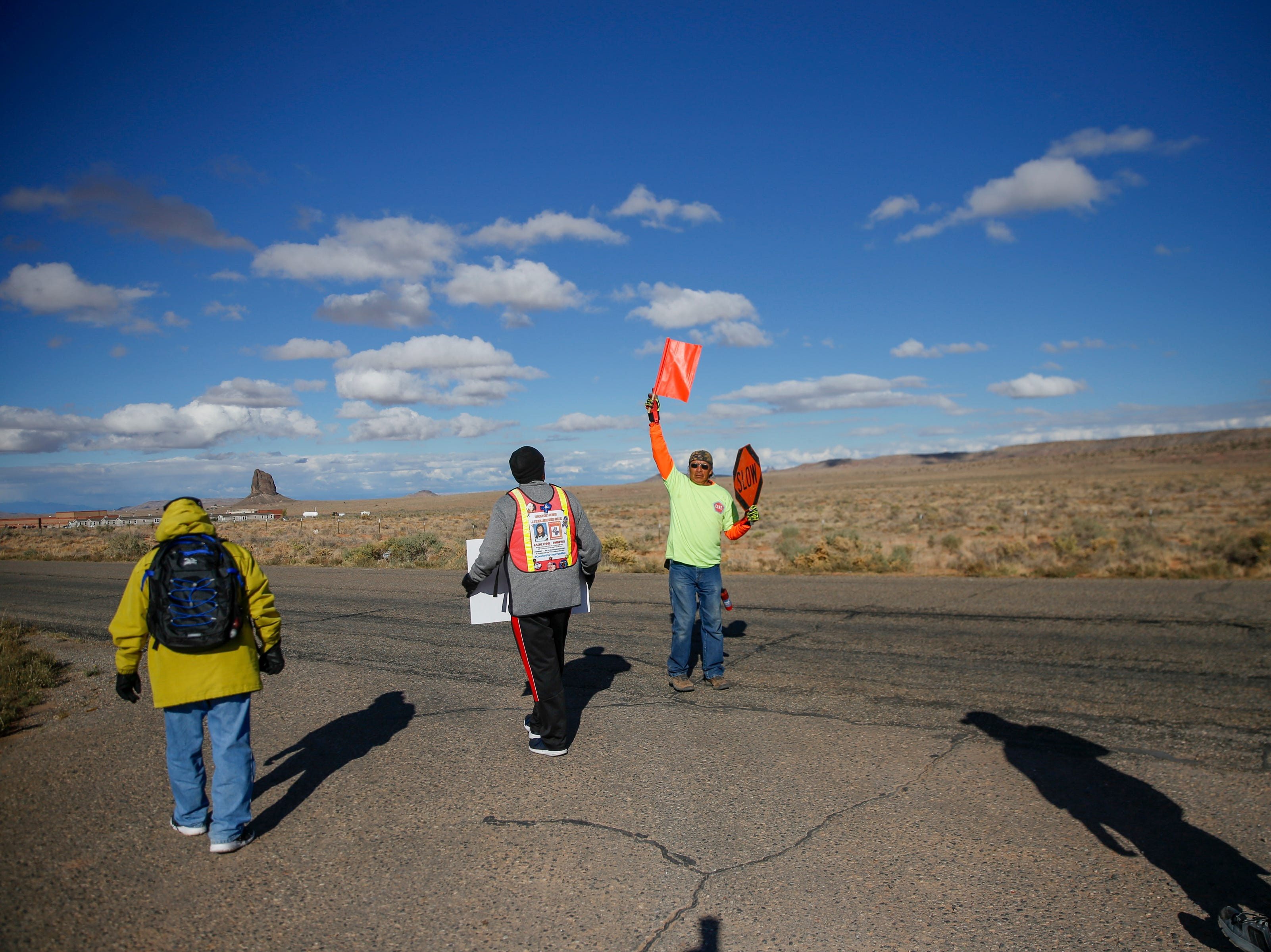 At center Darryl Begay a member of Red Valley Chapter's Community Emergency Response Team provides safety for the walkers Thursday, Oct. 18, 2018 along Navajo Route 13 in Red Valley, Arizona.
