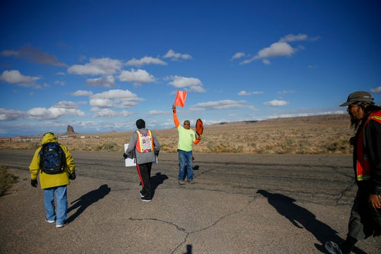 Darryl Begay, center, a member of Red Valley Chapter's Community Emergency Response Team, provides safety accompaniment for walkers Thursday along Navajo Route 13 in Red Valley, Ariz.
