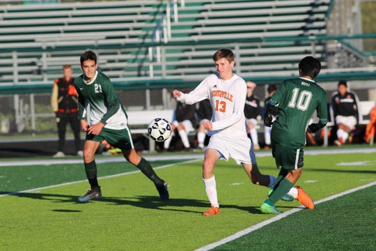 Northville's Sean Sullivan goes after the bouncing ball. Closing in are Novi players Gonzalo Sanz Cristobal (23) and Taiga Shiokawa (10).