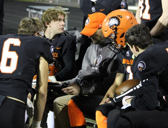 Brother Rice quarterbacks coach John Gieselman (sitting with gray coat) reviews some offense formations on the I-Pad with a few offensive players.