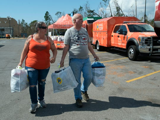 Heather Cunningham and her father, Jack Cunningham, retrieve their laundry after having it washed, dried and folded Friday, Oct. 19, 2018, as part of the Loads of Hope disaster relief Program in Callaway.