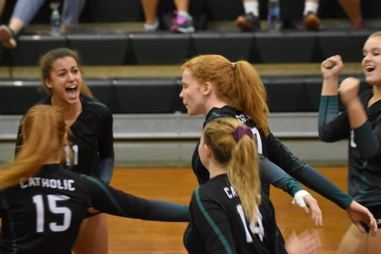 Catholic players Amiah Butler (11), Margaret Richrdson (15), Emmy Chambers (14) and Hannah Meyers (17) celebrate after a point earned during Thursday's District 1-5A Tournament win against West Florida.