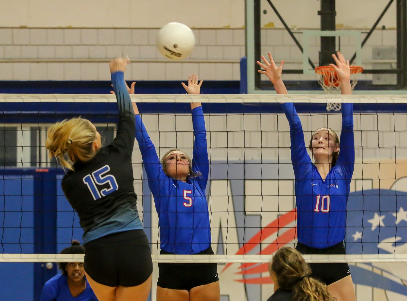 Washington's Brantley Haferkamp (15) gets the ball passed Pace's Grace McCammon (5) and Willow Sinkus Blackburn (10) in the District 1-7A championship game at Pace High School on Thursday, October 18, 2018. The Patriots beat the Wildcats in three straight sets and earned their second district title in a row.