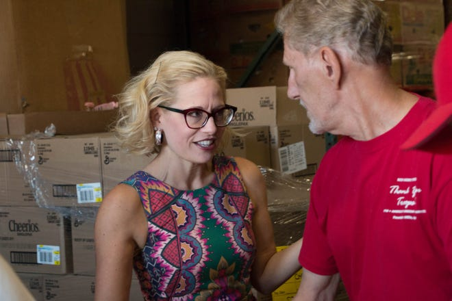 Kyrsten Sinema helps prepare snack packs with veteran Terry Araman at Desert Mission Food Bank, October 19, 2018.