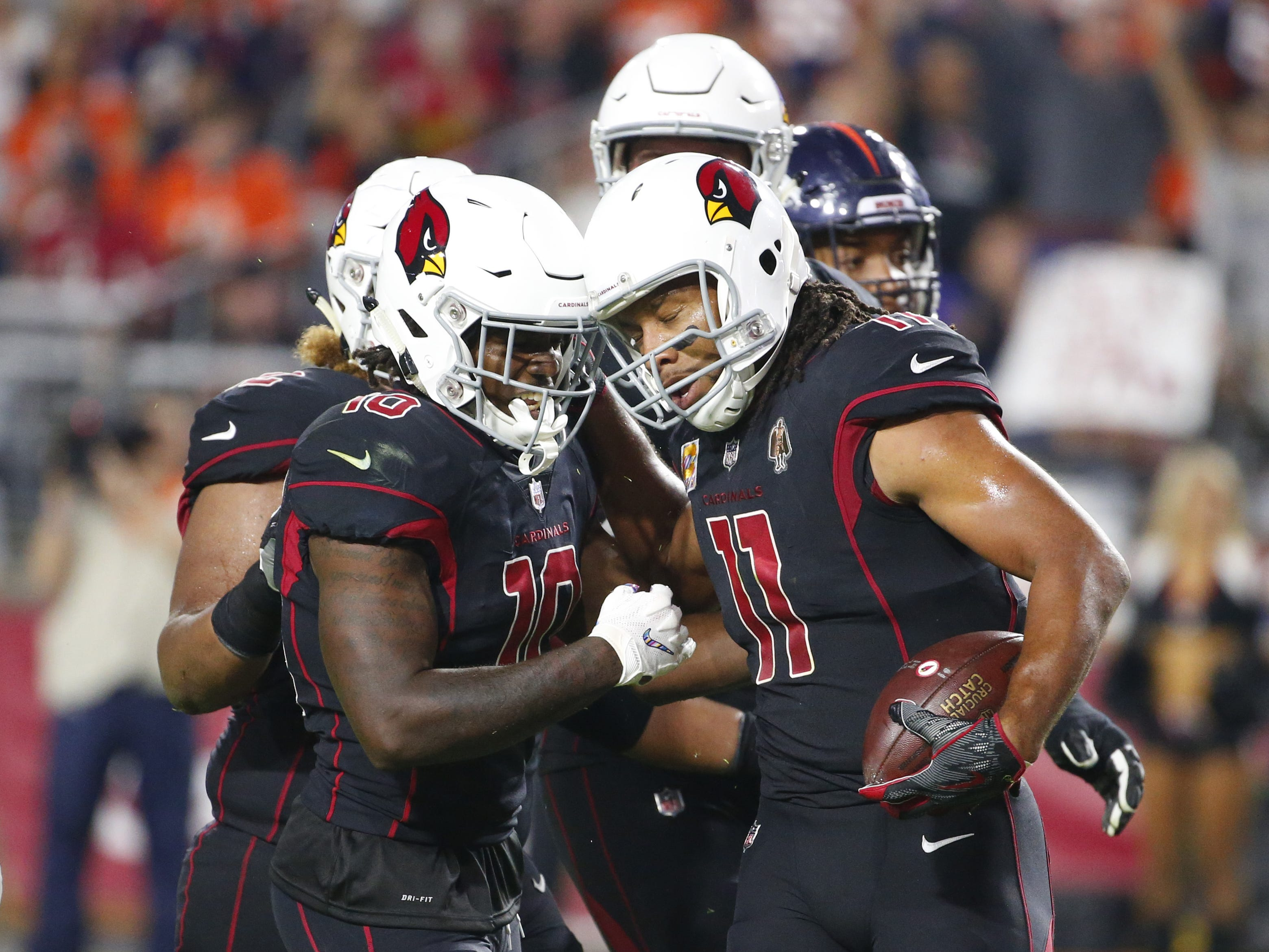 Arizona Cardinals wide receiver Larry Fitzgerald (11) celebrates his touchdown with his teammates during a football game against the Denver Broncos at State Farm Stadium in Glendale on October 18, 2018.