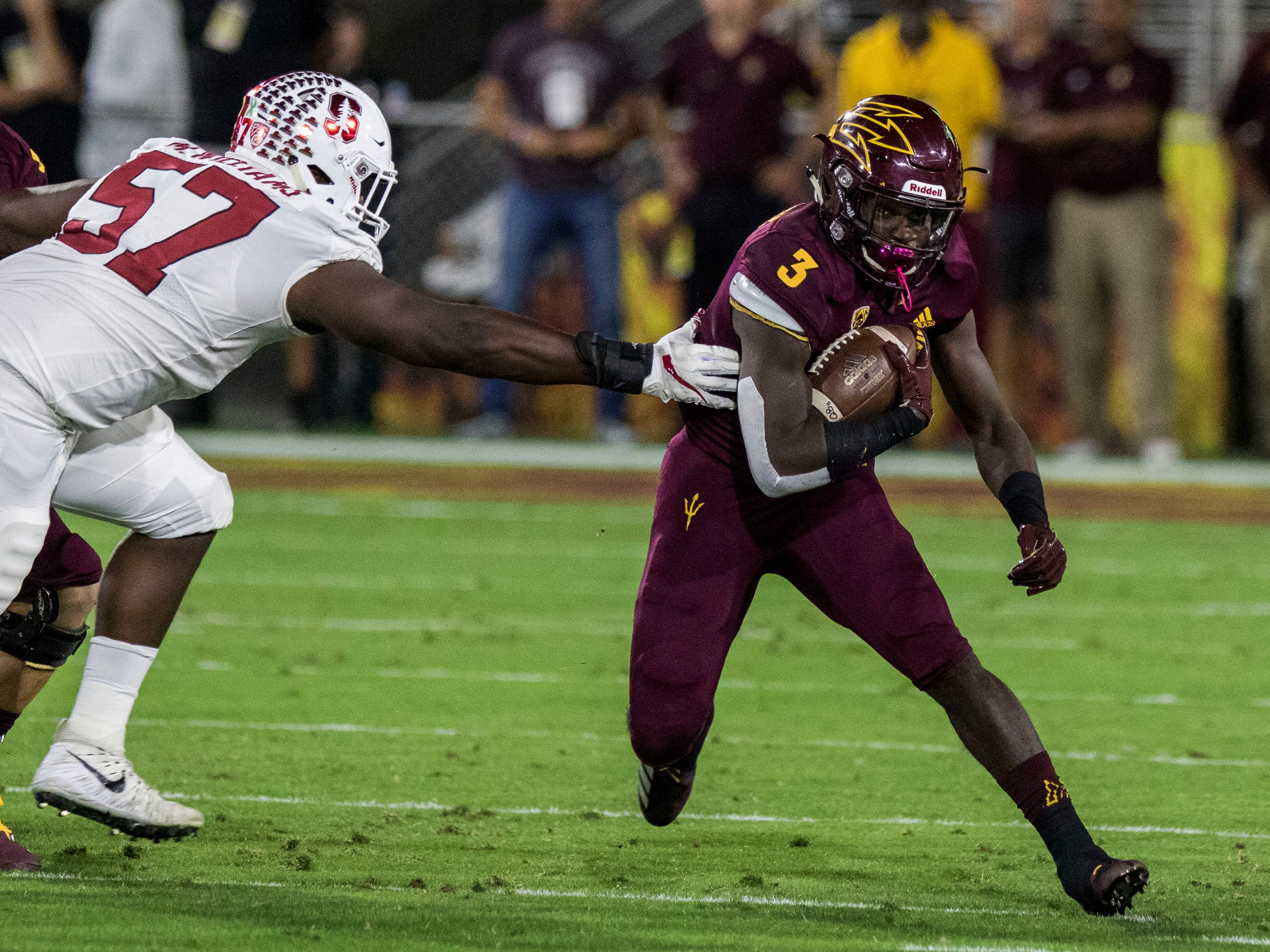 Arizona State's Eno Benjamin slips past Stanford's Michael Williams during the first half of an NCAA college football game Thursday, Oct. 18, 2018, in Tempe, Ariz.