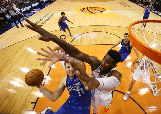 Phoenix Suns rookie center Deandre Ayton pressures the shot by Dallas Mavericks rookie Luka Doncic during the season opener at Talking Stick Resort Arena on Oct. 17, 2018, in Phoenix, Ariz.