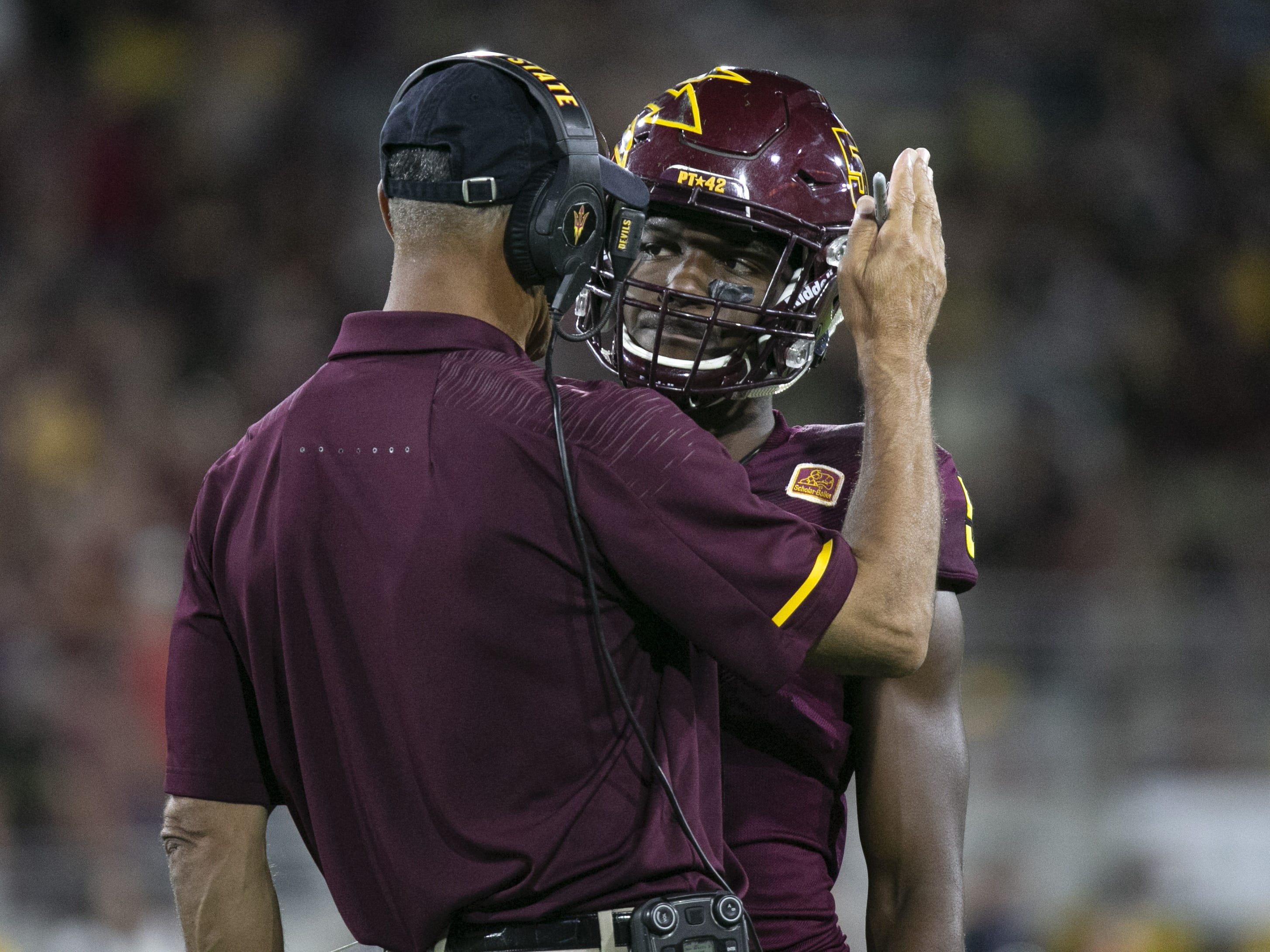 ASU head coach Herm Edwards talks to ASU defensive back Kobe Williams during the first half of the Pac-12 college football game against Stanford at Sun Devil Stadium in Tempe on October 18, 2018.