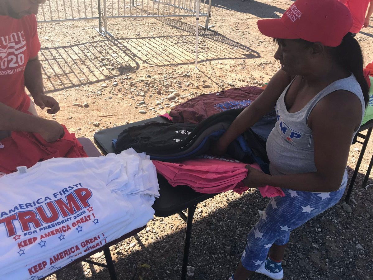 Vendors sell merchandise celebrating President Donald Trump, who is set to speak at a rally in Mesa, on Oct. 19, 2018. Many of them follow Trump from rally to rally, visiting dozens of cities each year.