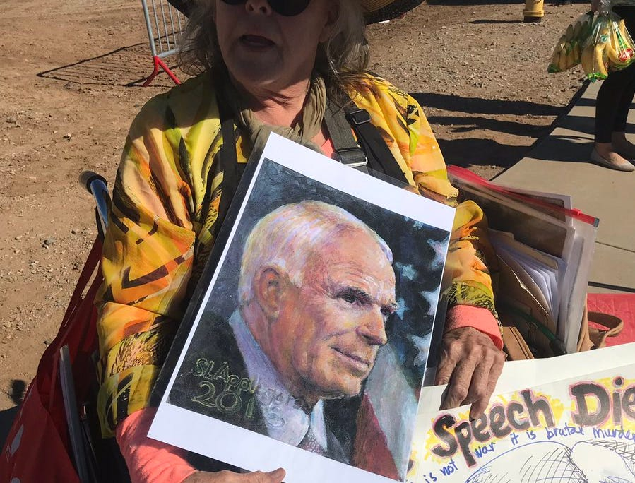 Susan Applegate, holding an image of the late U.S. Sen. John McCain, is the lone President Donald Trump protester so far mid-morning on Oct. 19, 2018. Officials have cordoned off a large section for protesters across the street from the line.