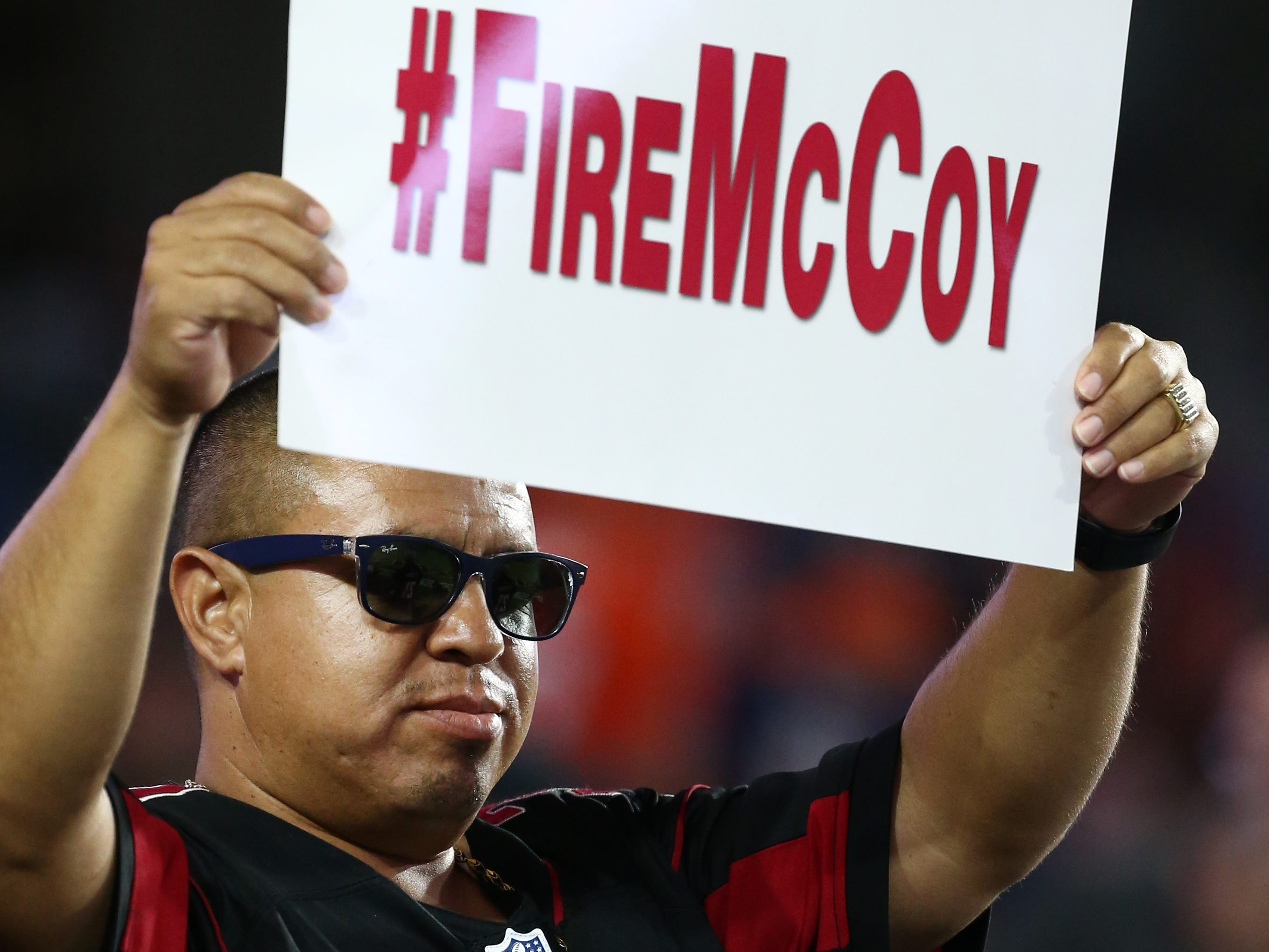 An Arizona Cardinals fan holds-up a sign #FireMcCoy in the first half at State Farm Stadium in Glendale, Ariz.