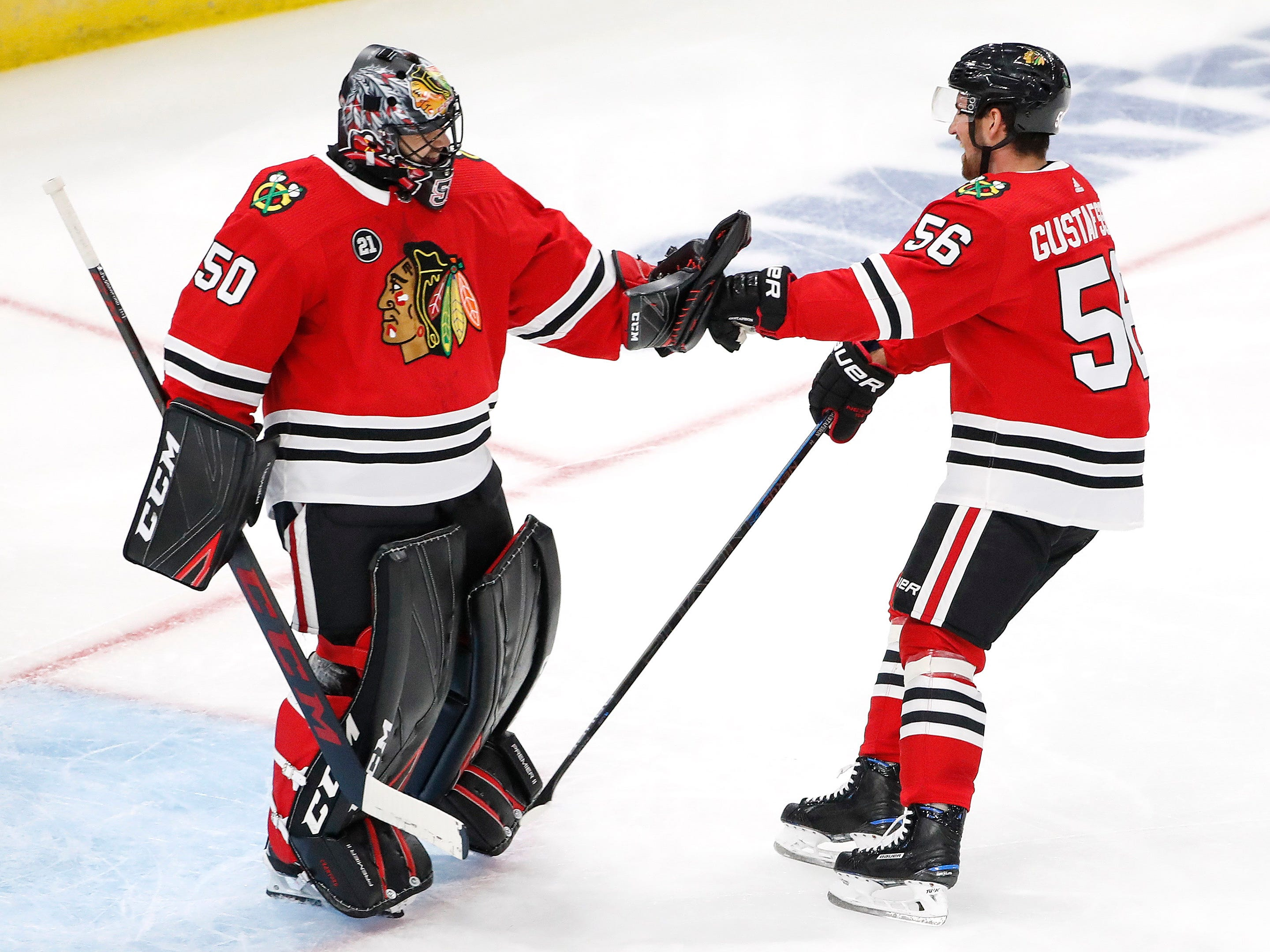 Oct 18, 2018; Chicago, IL, USA; Chicago Blackhawks defenseman Erik Gustafsson (56) celebrates with goaltender Corey Crawford (50) after scoring against the Arizona Coyotes during the second period at United Center.