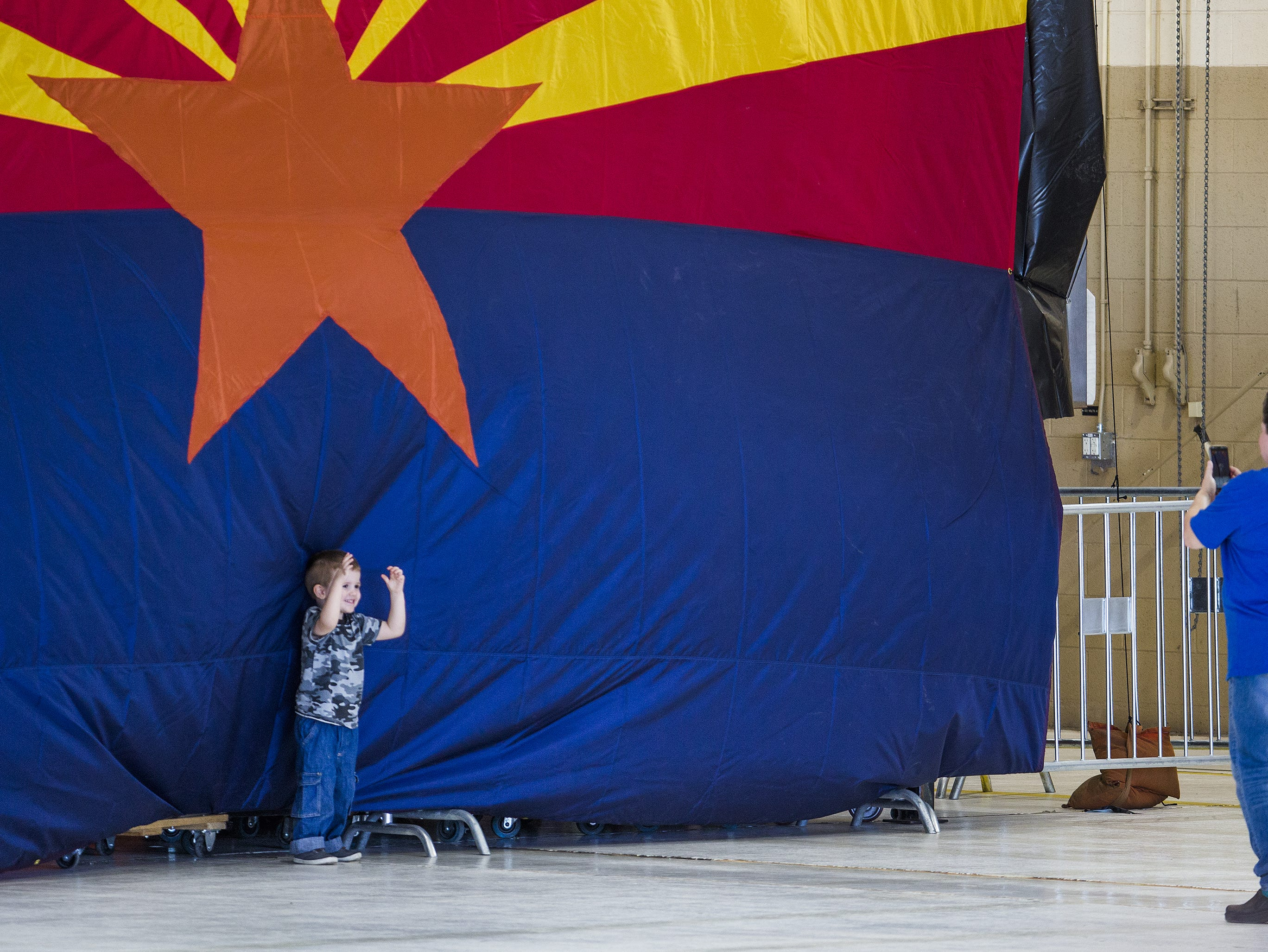 People take photos inside the International Air Response Hangar at Phoenix Mesa Gateway Airport on Oct. 19, 2018. The crowd had several hours to wait for President Donald Trump to appear Friday evening for a rally supporting Senate candidate Martha McSally.