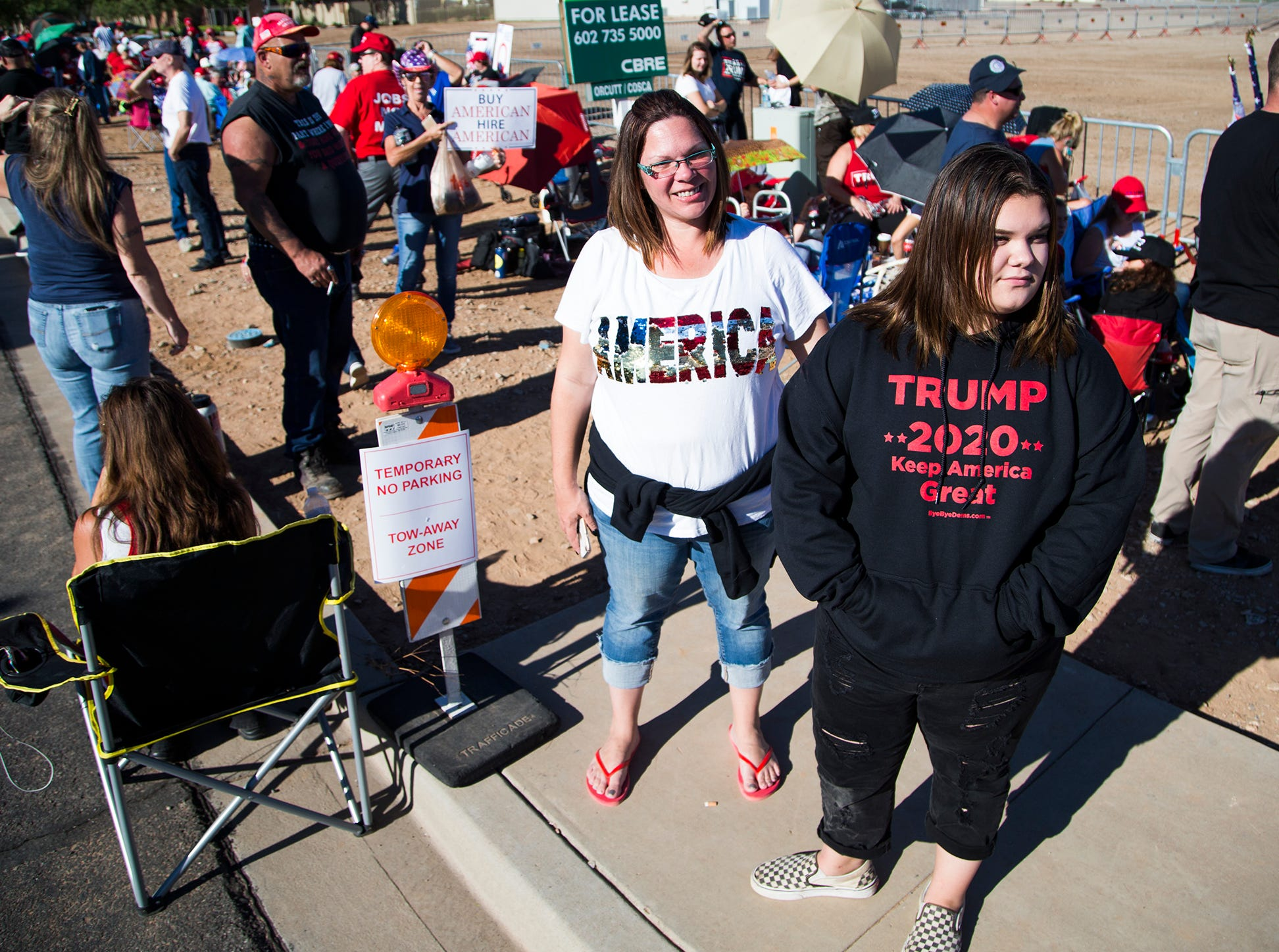 Kristin White (left) and her daughter, Madison Mederios, 13, both of the San Tan Valley area, wait in line to enter the International Air Response Hangar at Phoenix-Mesa Gateway Airport Oct. 19, 2018.  President Donald Trump will appear Friday evening for a rally supporting Senate candidate Rep. Martha McSally.