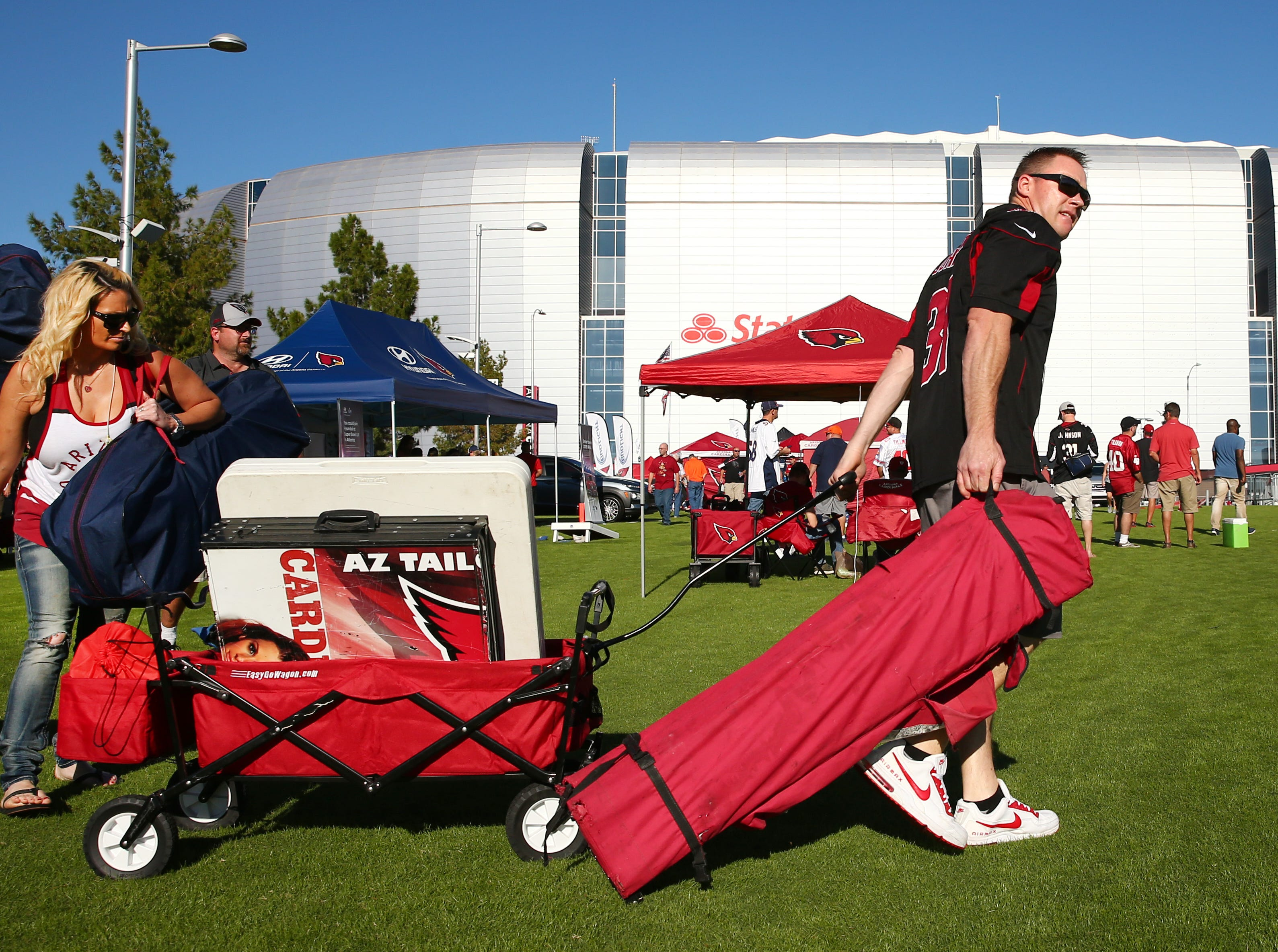 Arizona Cardinals fans April Ward (left) and Jason Stewart from Cottonwood arrive to tailgate 90-minutes before kick-off against the Denver Broncos due to traffic delays at State Farm Stadium in Glendale, Ariz.