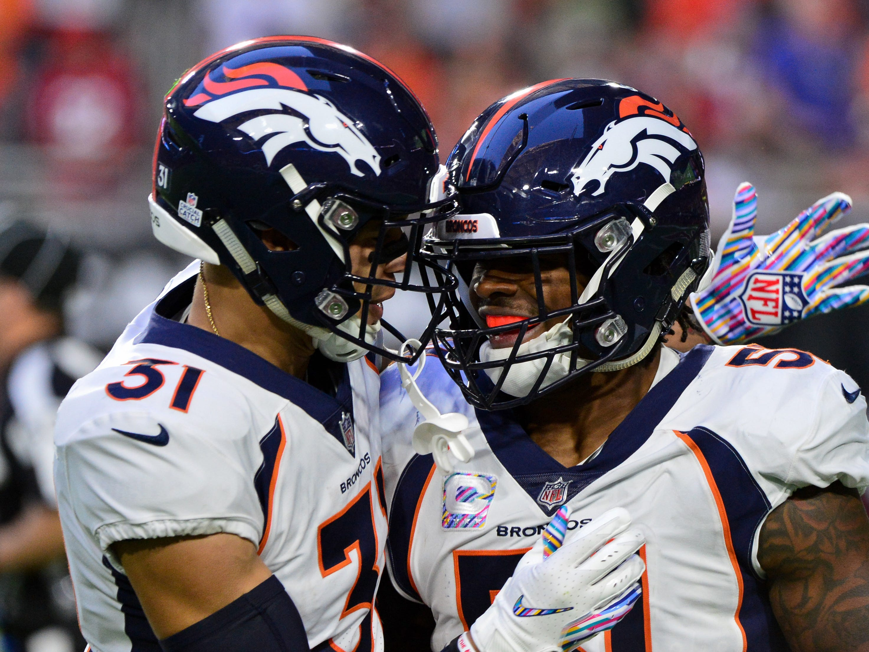 Oct 18, 2018; Glendale, AZ, USA; Denver Broncos linebacker Todd Davis (51) celebrates with free safety Justin Simmons (31) after returning an interception for a touchdown during the first half against the Arizona Cardinals at State Farm Stadium.
